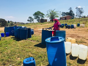 Photo of woman waiting with water containers
