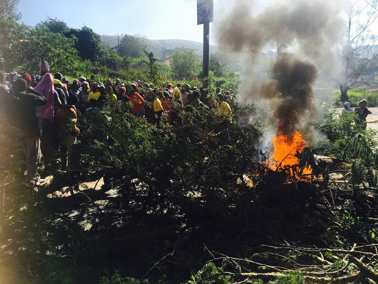 photo of burning tyres and branches in the road