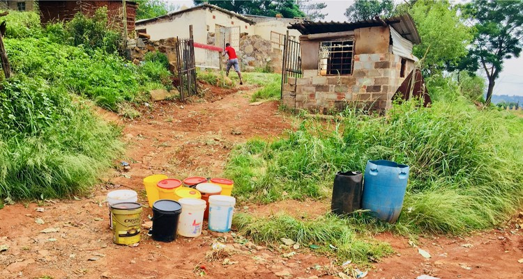 Photo of empty water containers outside a house
