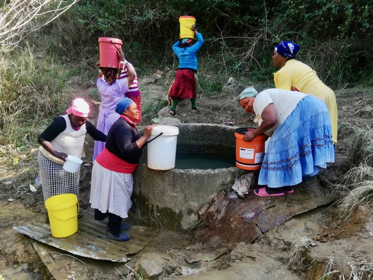 Photo of women fetching water with buckets