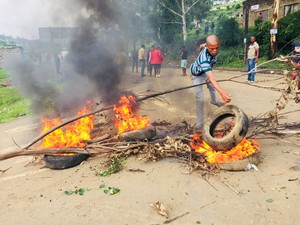 Photo of man throwing tyre onto fire