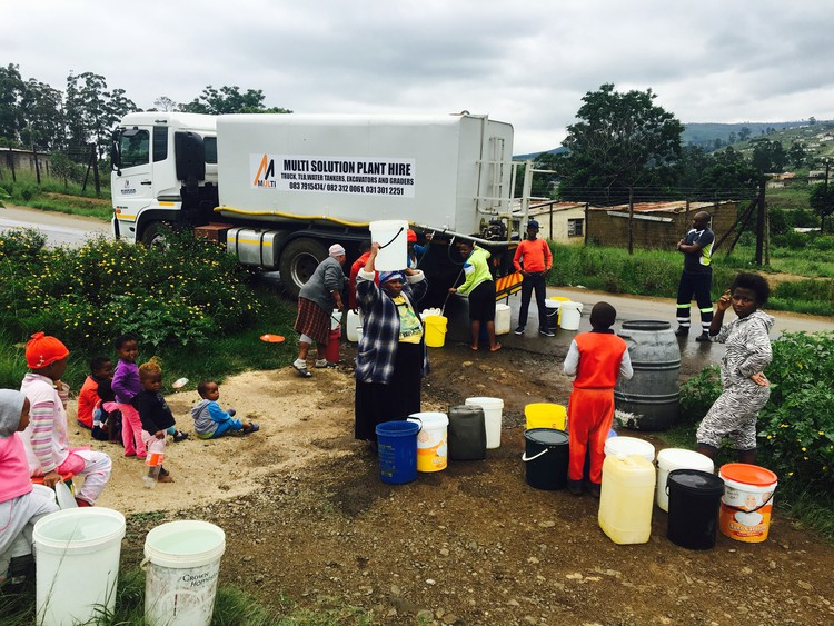 Photo of truck and people collecting water from it