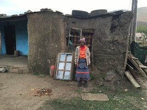 Photo of a woman in front of a mud house