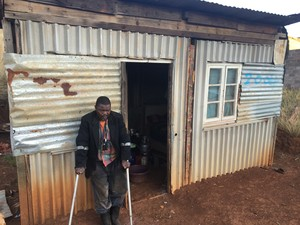 Photo of man with crutches in front of his shack