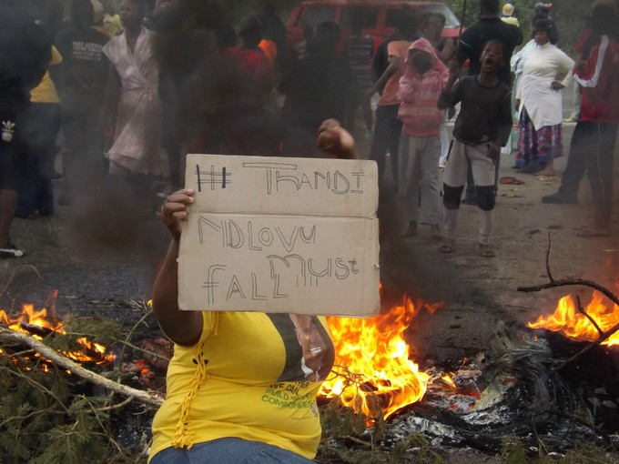 Photo of protester with placard saying Thandi Ndlovu must fall, in front of burning materials