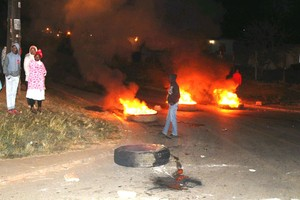 Photo of burning tyres and people standing around