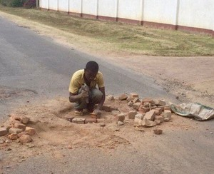 A man fixing a pothole