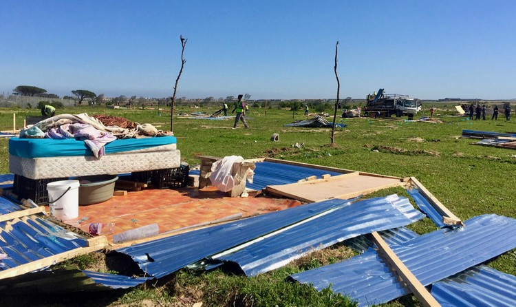Photo of demolished shacks in a field