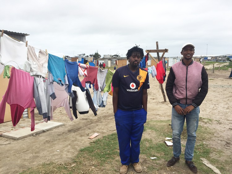 Photo of two men near a shack with washing on a line