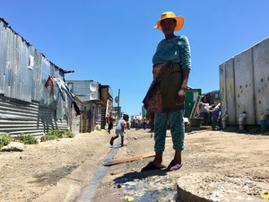 Photo of shacks and a polluted street