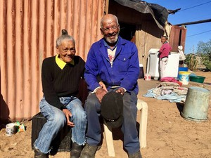 Photo of two old people in front of a shack