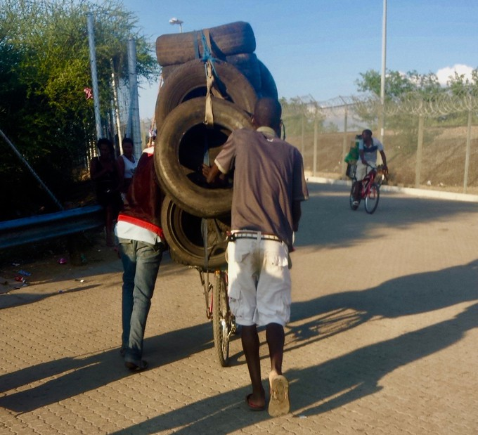 Photo of young men pushing a bicycle loaded with car tyres