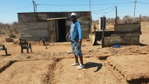 Photo of woman standing over the site where her house is to be built