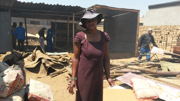 Photo of woman in front of shack