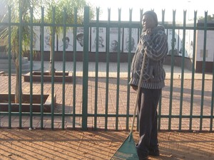 "Photo of William Sifumba in front of monument to ""Upington 26""."