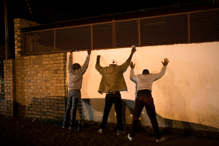 Photo of three men against a wall