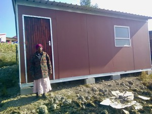 Photo of a woman in front of a prefab house