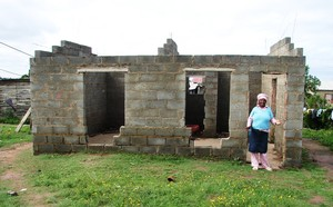 Photo of woman infront of an incomplete building