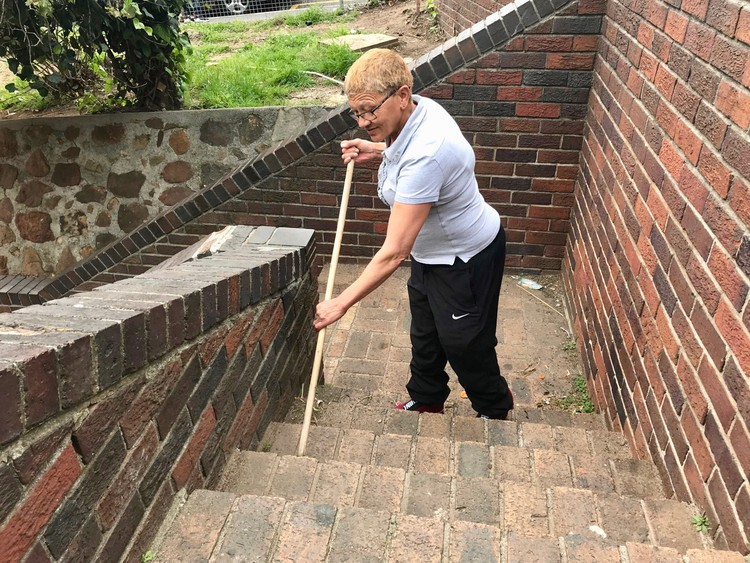 Photo of a woman sweeping stairs