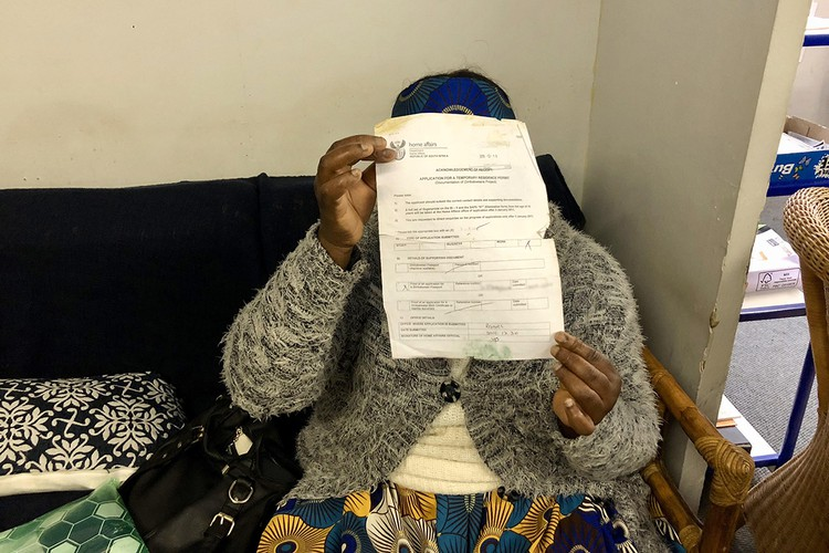 Photo of a person holding up documents