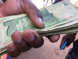 Photo of Zimbabwe bond notes being exchanged