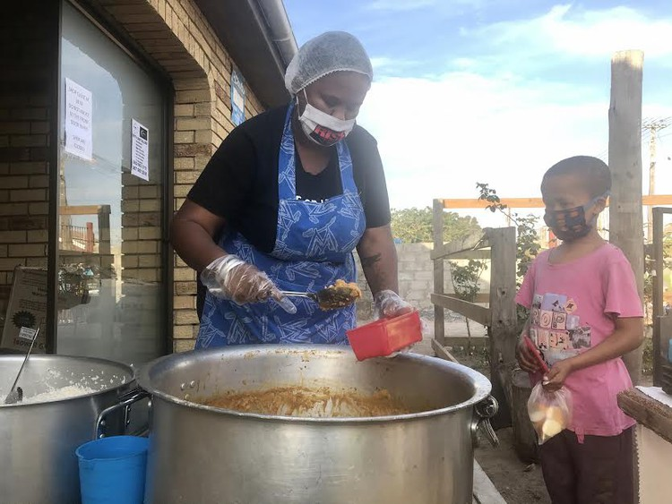 Latifa Jacobs hands out food to a child at the soup kitchen in Kuilsriver. Photo: Tariro Washinyira