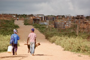 Photo of two people in front of many shacks