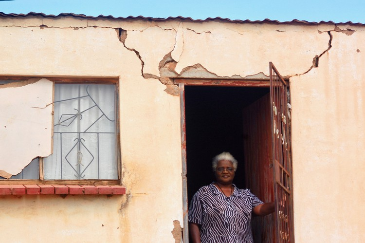 Photo of a woman in the doorway of her house