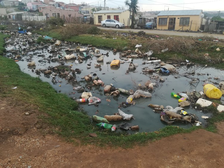 Photo of sewage flowing past houses