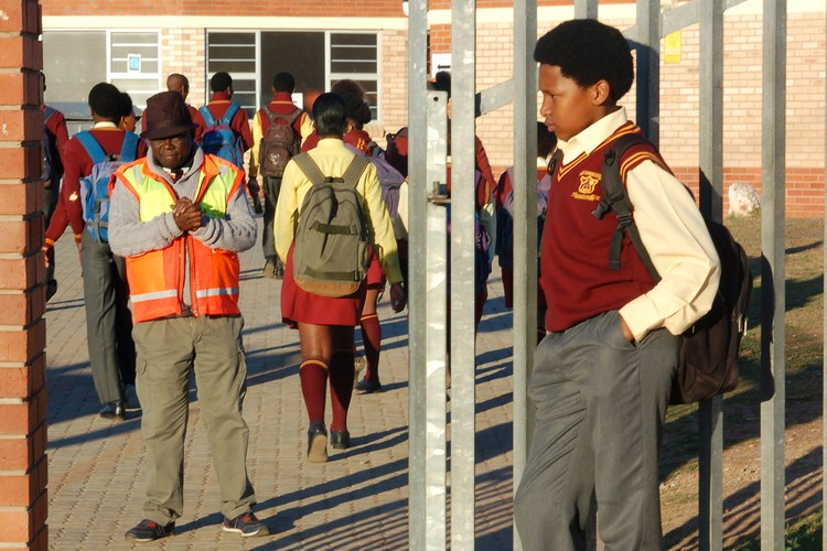Photo of learner with Afro outside his school\'s gate.