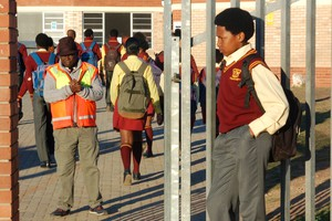 Photo of learner with Afro outside his school's gate.