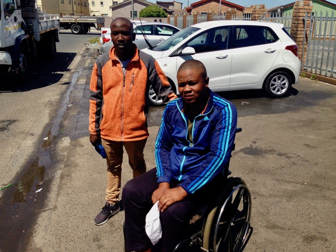 Photo of two men, one in a wheelchair