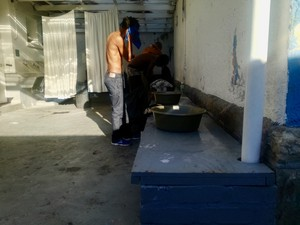 Photo of a man washing himself from a bucket