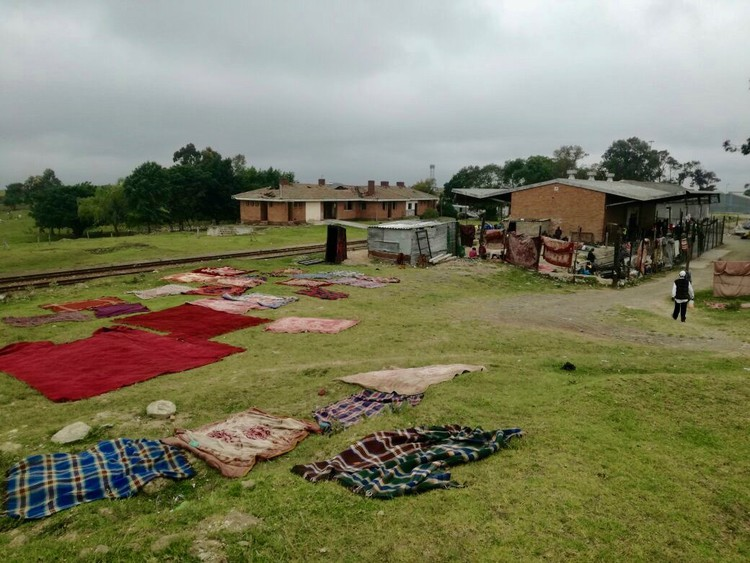Photo of a building and blankets drying outside