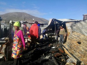 Photo of burnt shacks and a woman