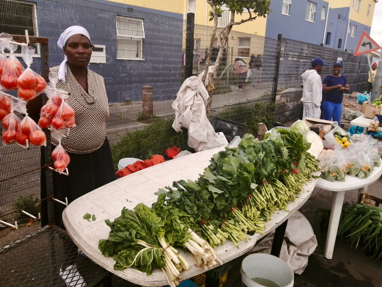Photo of a woman at her vegetable stand
