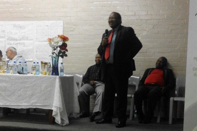 Photo of Advocate Vusi Pikoli speaking with a man sleeping behind him