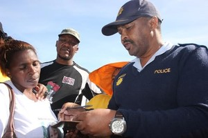 Photo of colonel Mkuseli Nkwitshi accepting a memorandum handed over by Vathiswa Dulaze and Andile Lili
