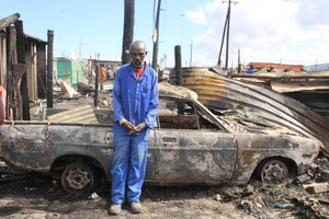 Photo of man in front of burnt car