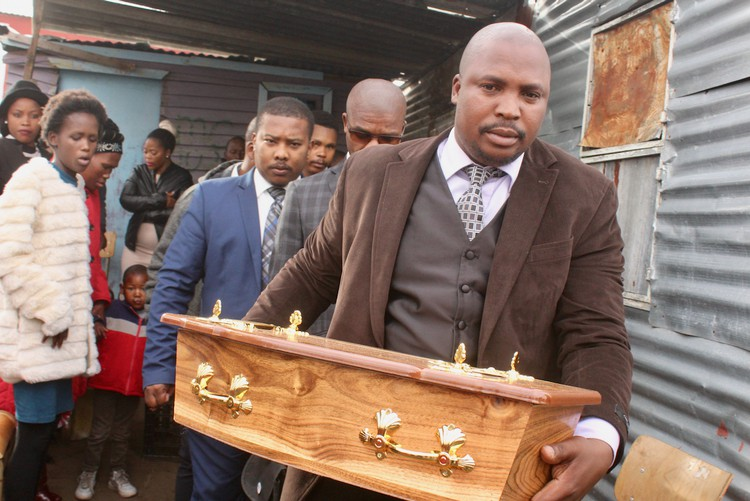 Photo of a man carrying a small coffin