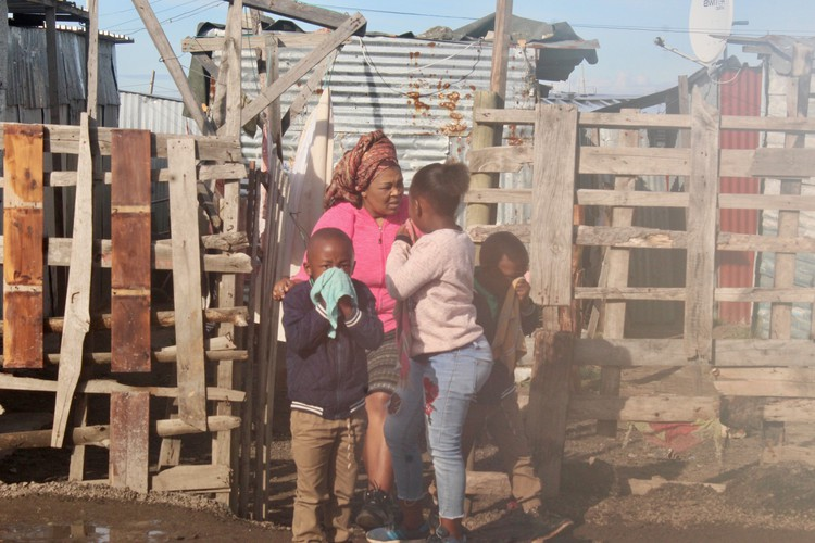A family tries is affected by teargas during a protest for services in Marikana informal settlement in Philippi East. - Velani Ludidi