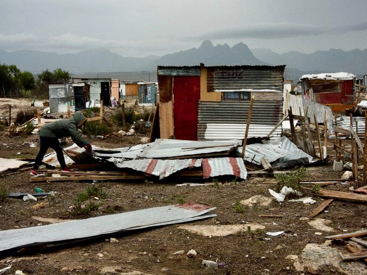 Photo of a demolished shack and a woman