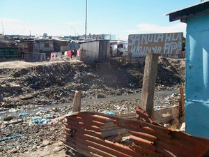 Photo of shacks and filthy water
