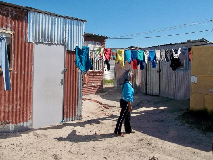 Photo of a woman outside a shack