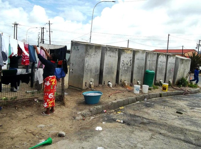 Photo of women hanging up washing near a row of toilets