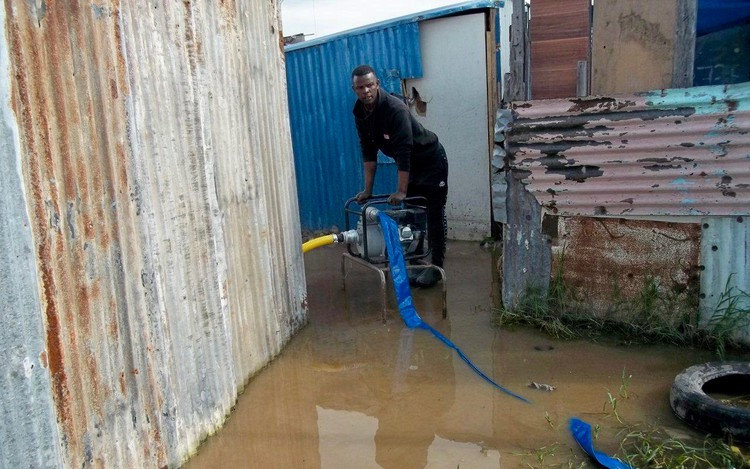 Photo of water being pumped from flooded shacks