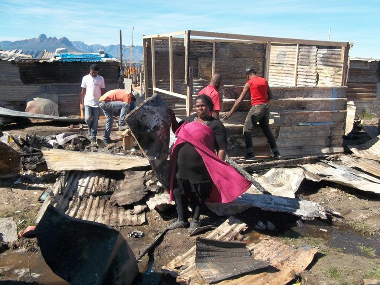 Photo of a woman with fire debris and shacks being built