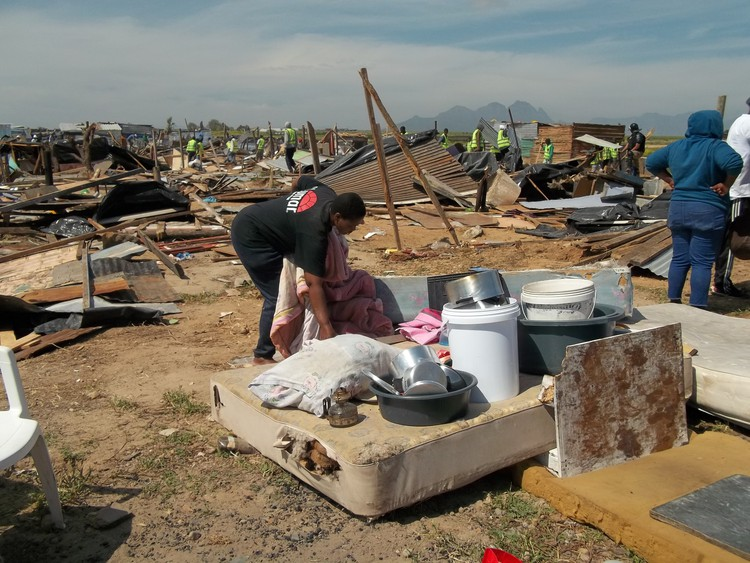 Photo of a woman and a demolished shack