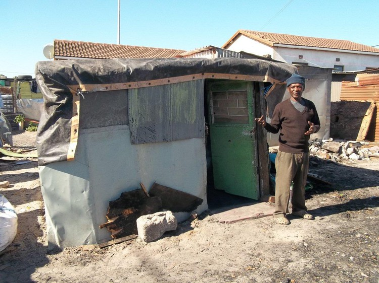 Photo of fire victim in front of his new shack