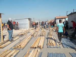 Photo of a person and shack building materials